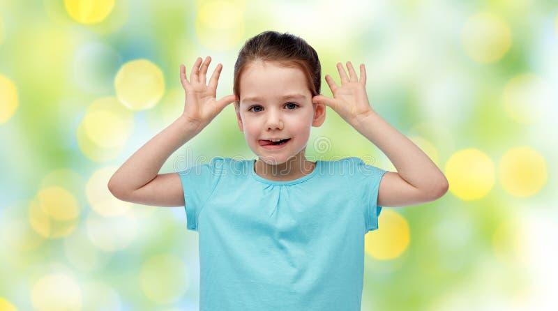 获得乐趣和做耳朵的愉快的小女孩 库存图片