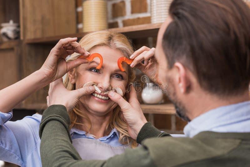 获得乐趣和做鬼脸与片断的妻子和丈夫 免版税图库摄影