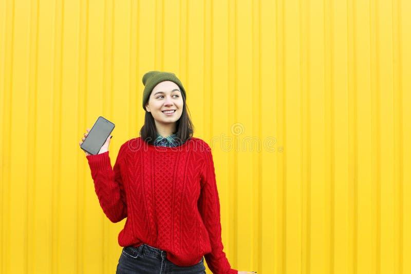 获得乐趣和做鬼脸的年轻时髦的行家女孩在明亮的黄色都市墙壁附近在与闪光的晚上 戴桃红色帽子,温暖 免版税库存图片