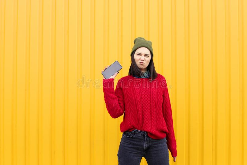 获得乐趣和做鬼脸的年轻时髦的行家女孩在明亮的黄色都市墙壁附近在与闪光的晚上 戴桃红色帽子,温暖 免版税库存照片
