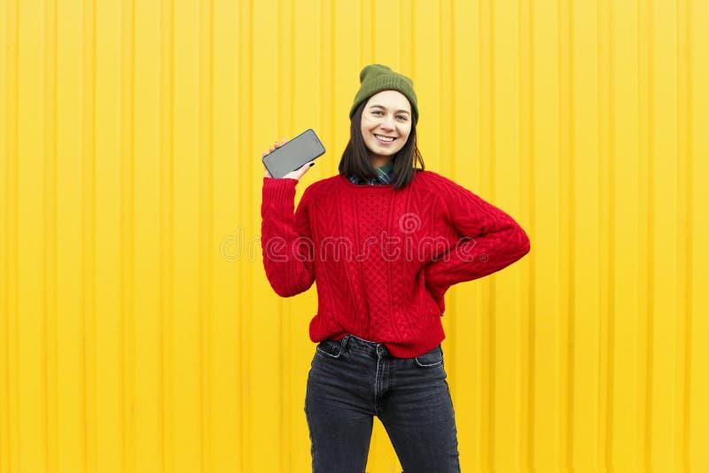 获得乐趣和做鬼脸的年轻时髦的行家女孩在明亮的黄色都市墙壁附近在与闪光的晚上 戴桃红色帽子,温暖 库存图片