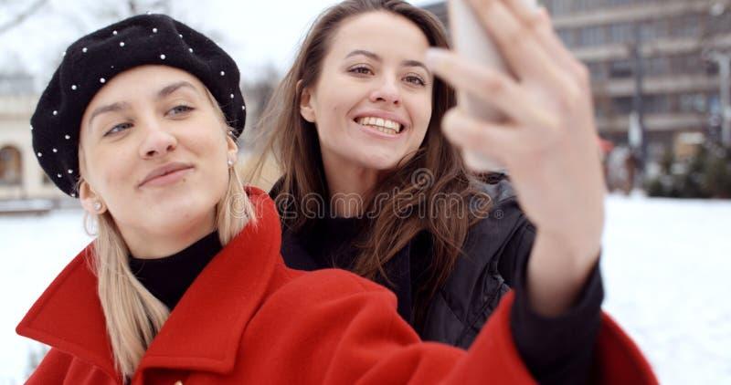 获得乐趣和做selfie的年轻快乐的女孩,户外 库存照片