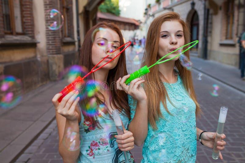 获得乐趣和吹泡影的两个俏丽的女孩 都市backgroun 库存照片