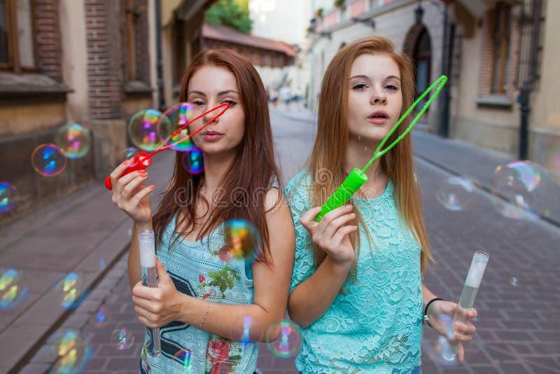 获得乐趣和吹泡影的两个俏丽的女孩 都市backgroun 免版税库存图片