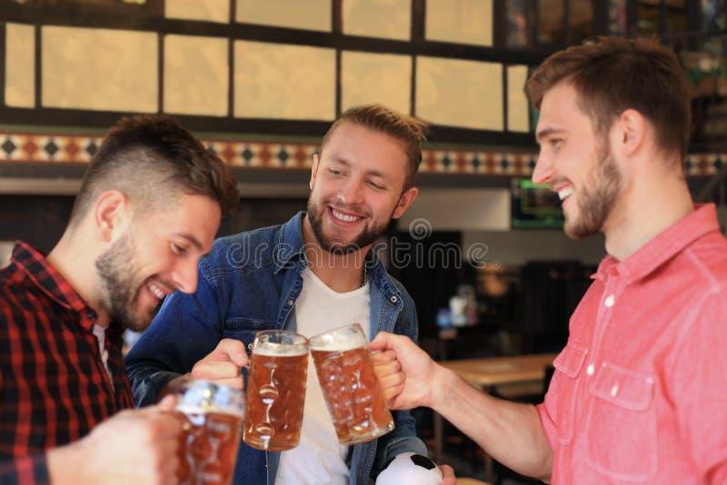获得乐趣和喝桶装啤酒的快乐的老朋友在酒吧柜台在客栈 免版税库存图片