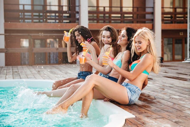 获得乐趣和喝鸡尾酒的四个女孩在游泳池 免版税库存照片