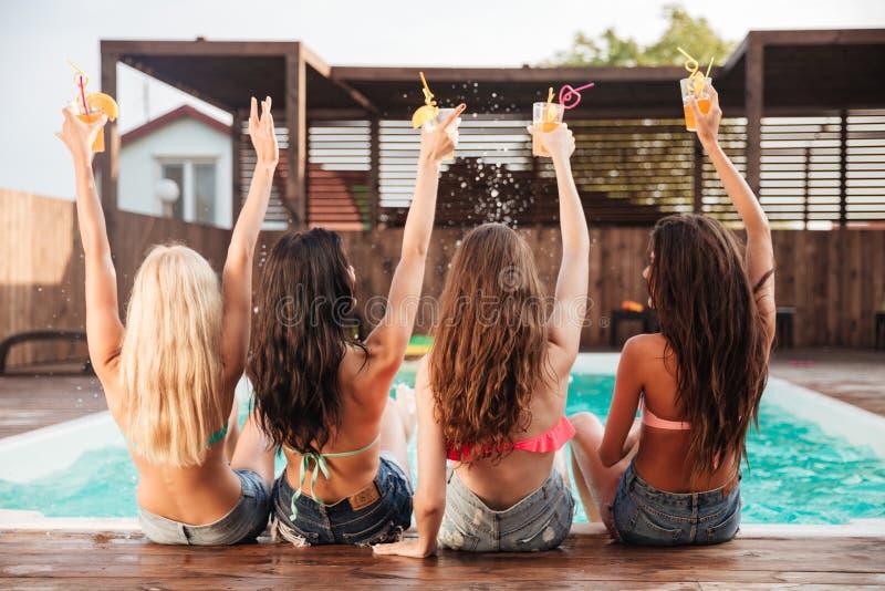 获得乐趣和喝鸡尾酒的四个女孩在游泳池 库存照片