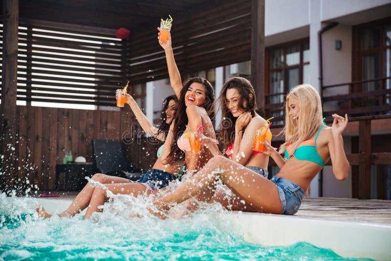 获得乐趣和喝鸡尾酒的四个女孩在游泳池 库存图片