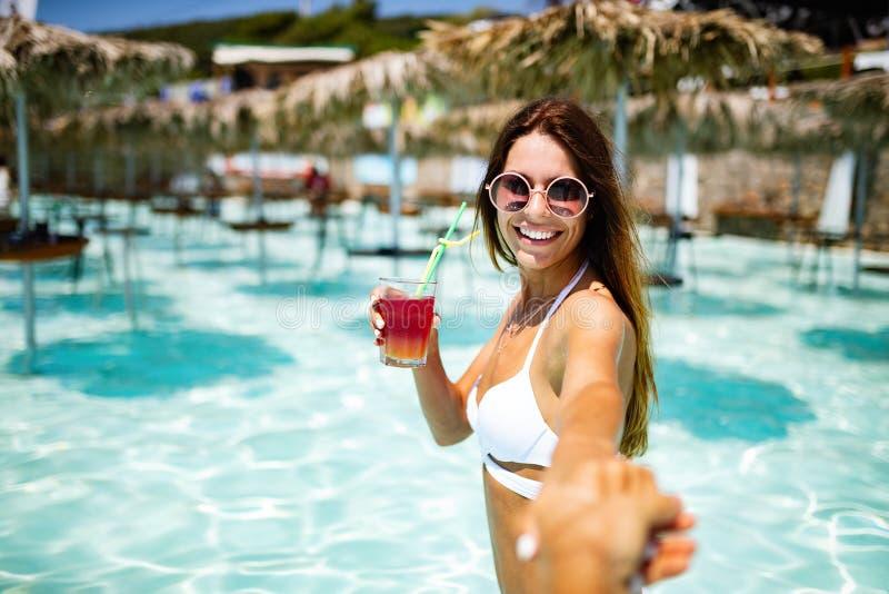 获得乐趣和微笑在海滩的暑假年轻女人在有鸡尾酒的比基尼泳装 免版税库存照片