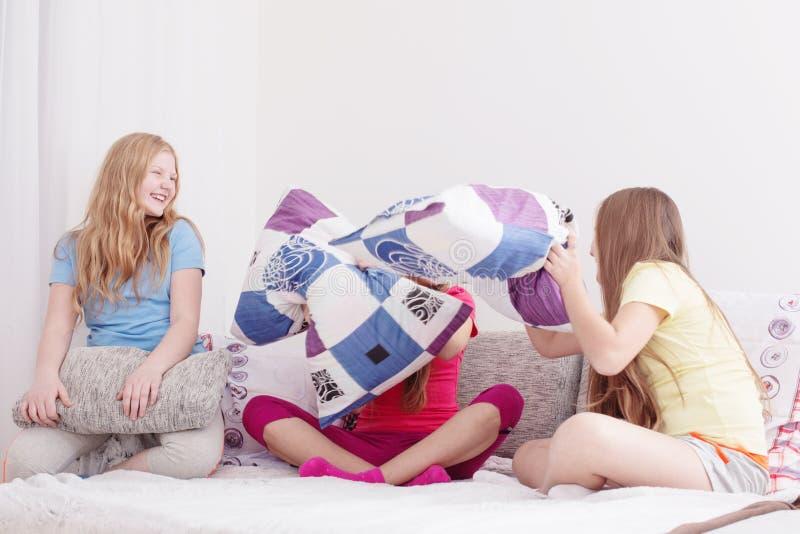 获得乐趣和战斗与枕头的十几岁的女孩 免版税库存照片