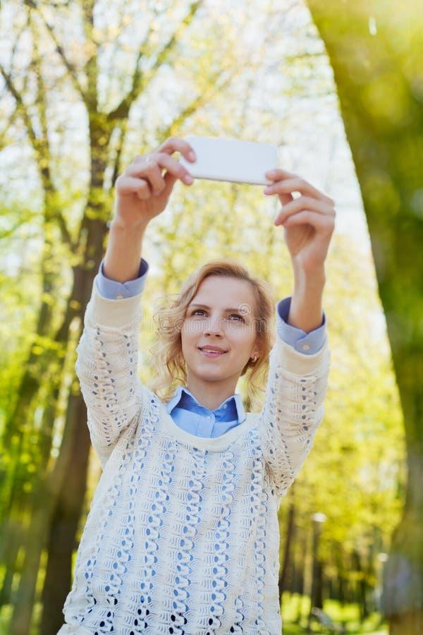 获得乐趣和拍在智能手机照相机的女孩学生selfie照片室外在绿色夏天公园在晴天,少年tran 免版税库存照片
