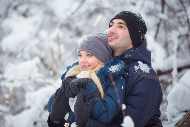 获得乐趣和拥抱户外在雪公园的愉快的夫妇 背景海滩异乎寻常的做的海洋沙子雪人热带假期白色冬天 库存照片