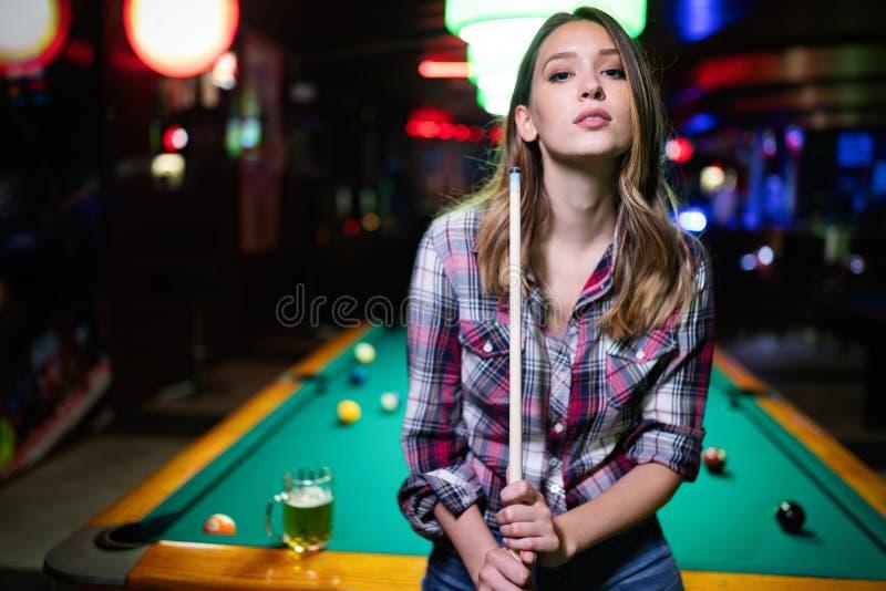 获得乐趣和演奏台球的年轻美女在俱乐部 免版税库存照片