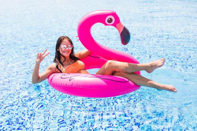 获得乐趣和笑在一个可膨胀的巨型桃红色火鸟水池浮游物床垫的女孩在比基尼泳装 可爱的被晒黑的妇女l 免版税图库摄影