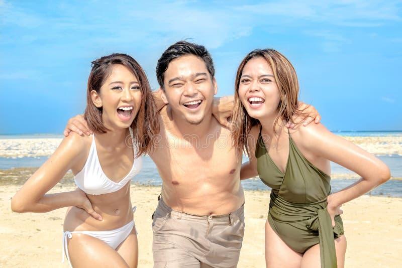 获得乐趣和笑在海滩的小组亚裔朋友 免版税库存照片