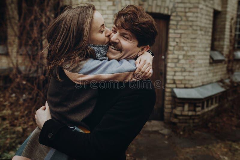 获得乐趣和笑在秋天公园的时髦的夫妇 人和w 免版税库存照片