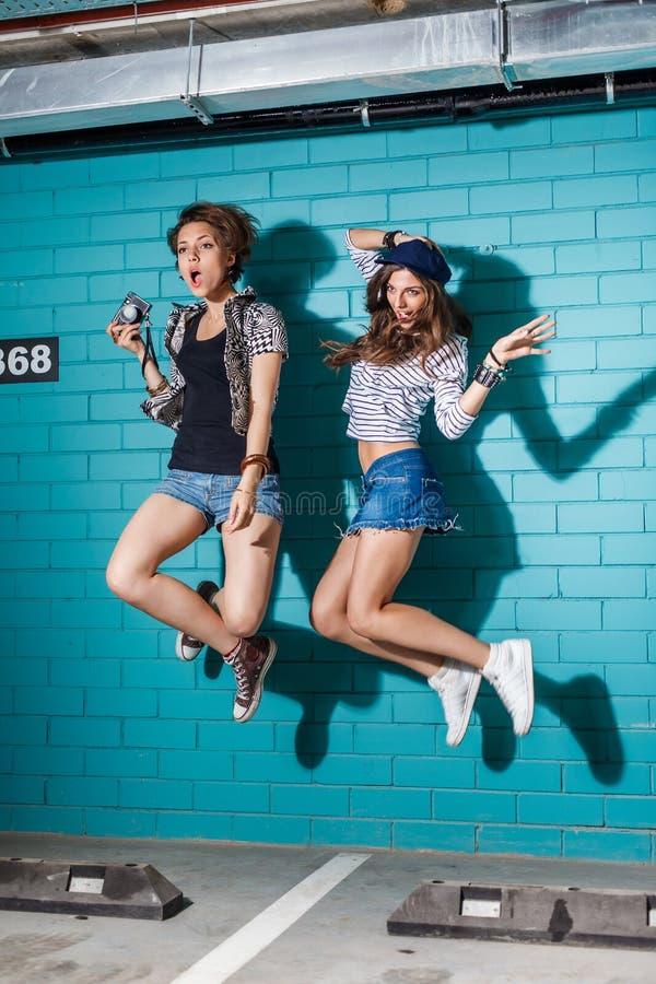 获得乐趣和跳跃在蓝色砖前面的愉快的青年人 库存照片