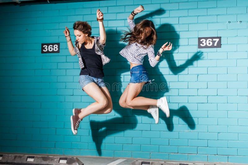 获得乐趣和跳跃在蓝色砖前面的愉快的青年人 库存图片