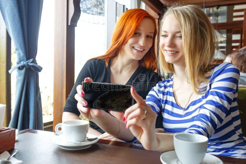 获得乐趣在咖啡馆和看巧妙的电话的两名妇女 库存照片