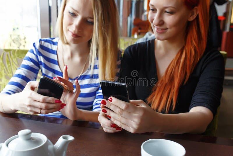 获得乐趣在咖啡馆和看巧妙的电话的两名妇女 库存图片