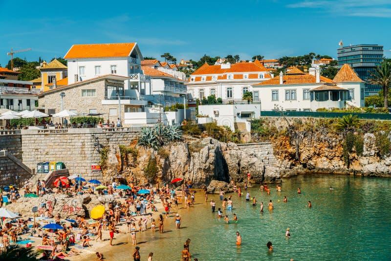 获得乐趣在水中,放松和晒日光浴在卡斯卡伊斯海洋葡萄牙的海滩胜地的游人 免版税图库摄影