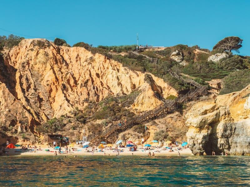 获得乐趣在水中,放松和晒日光浴在普腊亚的游人在拉各斯做卡米洛骆驼海滩在葡萄牙 免版税库存照片