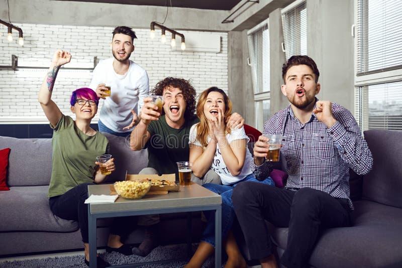 获得乐趣看电视的一个小组朋友在屋子里 免版税库存图片