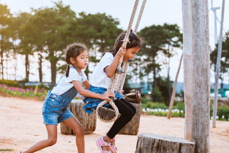 获得亚裔儿童的女孩乐趣使用在与她的姐妹的木摇摆在有美好的自然的操场 库存图片