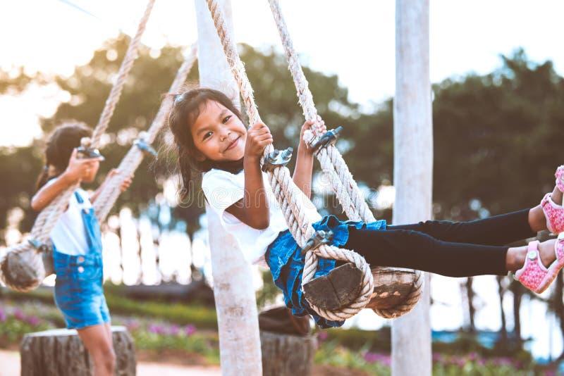 获得亚裔儿童的女孩乐趣使用在与她的姐妹的木摇摆在有美好的自然的操场 免版税库存照片