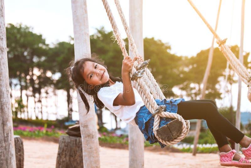 获得亚裔儿童的女孩乐趣使用在木摇摆在有美好的自然的操场 图库摄影
