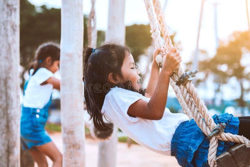 获得亚裔儿童的女孩乐趣使用在木摇摆在有美好的自然的操场 免版税库存照片