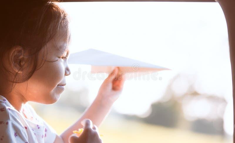 获得亚裔小孩的女孩乐趣使用与纸飞机 库存照片