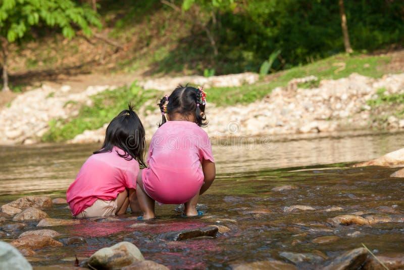 获得儿童两的女孩乐趣一起使用在瀑布 免版税库存图片