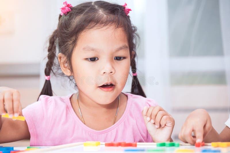 获得儿童的女孩学会的乐趣演奏和磁性字母表 免版税库存图片