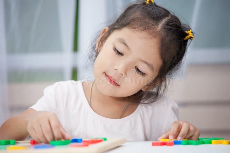 获得儿童的女孩学会的乐趣演奏和磁性字母表 免版税图库摄影