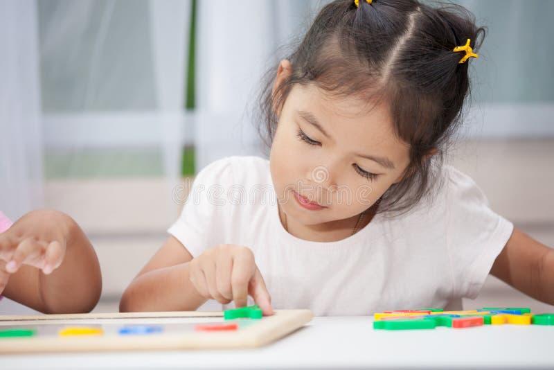 获得儿童的女孩学会的乐趣演奏和磁性字母表 免版税库存照片