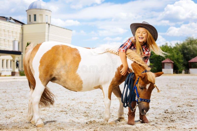 获得发笑牛仔的女孩与小马的乐趣槽枥外 免版税图库摄影