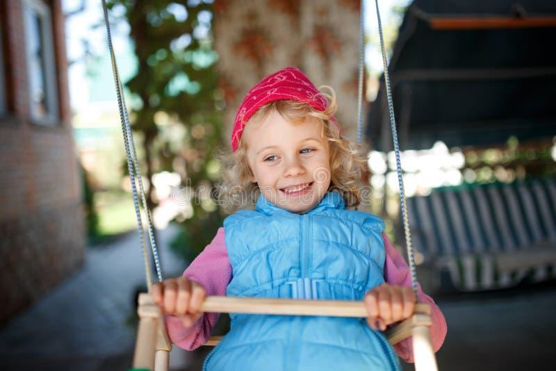 获得可爱的小女孩在室外的摇摆的乐趣 免版税库存图片