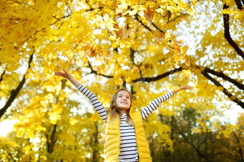 获得可爱的少女乐趣在美好的秋天天 使用在秋天公园的愉快的孩子 孩子汇聚黄色秋叶 免版税库存图片