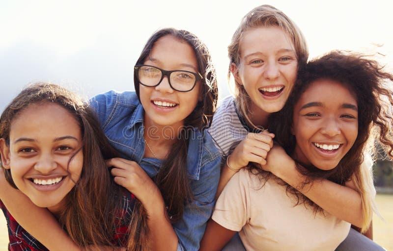 获得四个的十几岁的女孩扛在肩上的乐趣户外 库存照片