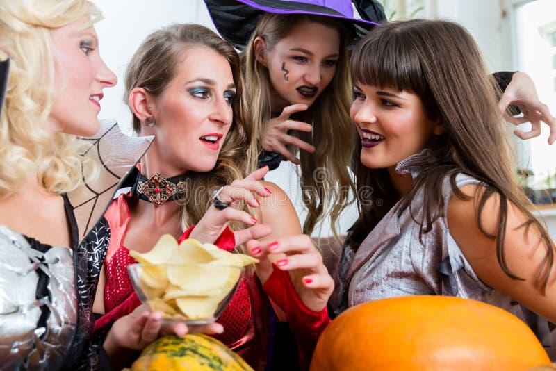 获得四名美丽的妇女乐趣,当一起时庆祝万圣夜 免版税库存照片
