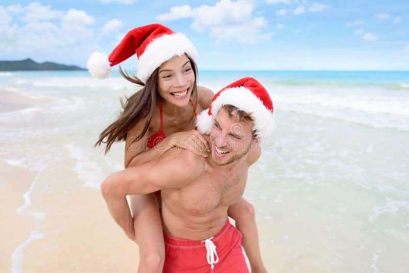 获得圣诞节的夫妇乐趣海滩假期 免版税库存图片
