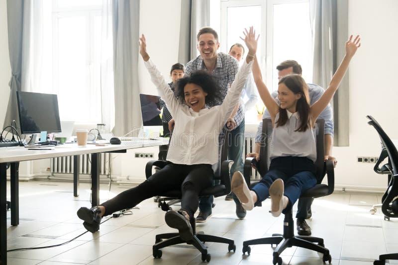 获得在星期五,不同的激动的工作者乘坐在椅子的乐趣 免版税库存照片