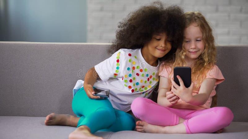 获得在沙发的乐趣和采取在智能手机的最佳的多种族朋友selfie 免版税库存图片