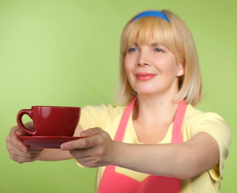 获得在红色盖帽的主妇茶 图库摄影