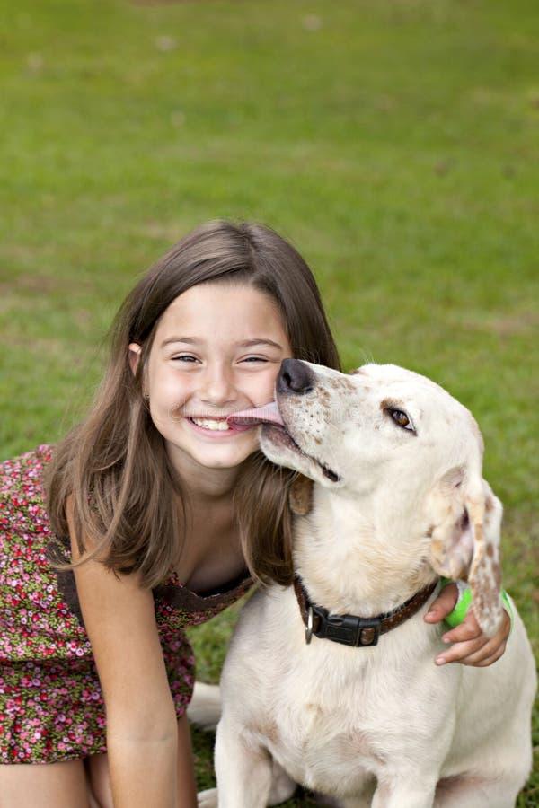 获得女孩亲吻一点的狗 库存图片