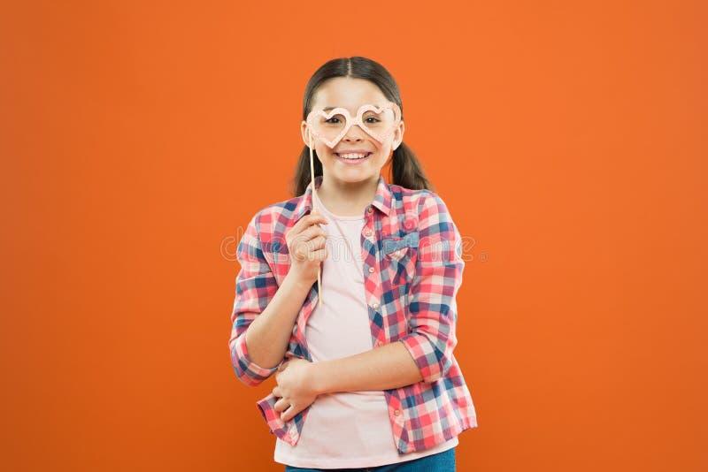 获得女孩的孩子乐趣 r 获得的愉快与照片摊支柱的乐趣 嬉戏的心情 请要 库存图片