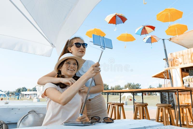 获得女孩的少年乐趣,做selfie照片 夏天街道咖啡馆,度假区,城市公园背景,青年生活方式 免版税库存图片