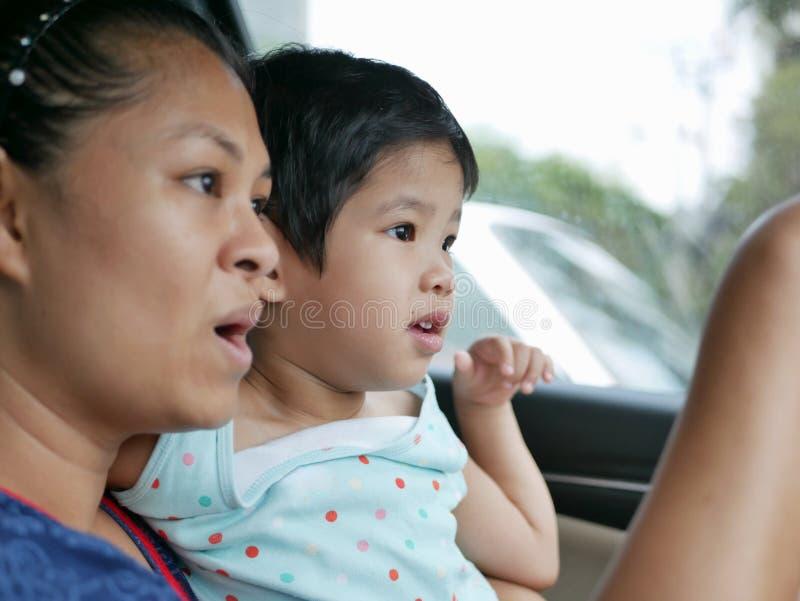 获得小亚裔的女婴旅行与她的母亲的乐趣乘汽车,她学会告诉在旅行期间,什么她看见 免版税图库摄影
