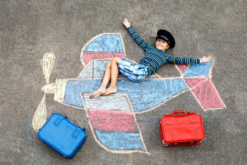 获得小孩的男孩与与飞机图片图画的乐趣与在沥青的五颜六色的白垩 与白垩的儿童绘画 库存图片